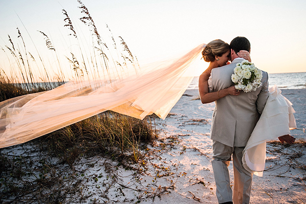 groom-carrying-his-bride-onto-the-sandy-beach-bridal-style-carry-romantic-beach-wedding-Paul-Johnson-Photography